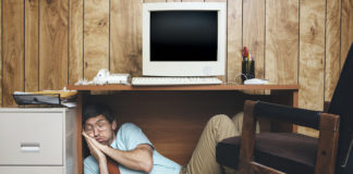 Guy who is working on his hangover cure A man and office in 1980's - 1990's style, complete with vintage computer and technology of the time, sleeps under his desk, too tired and bored to continue working. Wood paneling on the wall in the background.