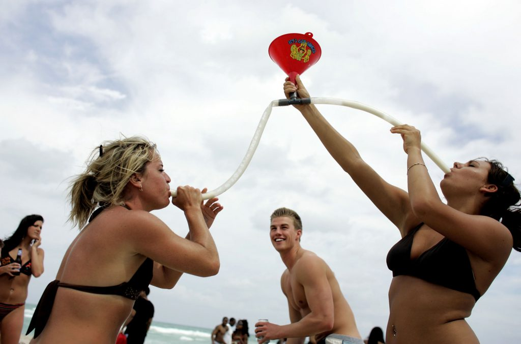 Spring break's veteran MIAMI BEACH- MARCH 14: Megan Jump (L) and Jenna Haring ,on spring break from Ball State University, use a funnel to drink beer March 14, 2007 on South Beach in Miami Beach, Florida. Students from universities and colleges around the country are attending spring break which ranges from the end of February to mid-April. (Photo by Joe Raedle/Getty Images)
